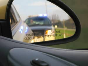 View from a driver's vehicle side mirror of a police car as they are getting pulled over
